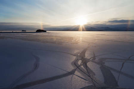 icefield: Landscape with natural drawing on snowed icefield and solar halo in the background
