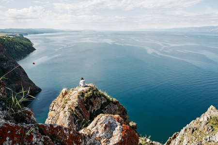 Brooding man sits on the edge of rock in front of the open water space, top view  Stock Photo