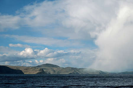 Big cloud in the form of mans face hangs down just over water and mountains