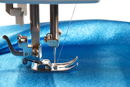 Sewing process, sewing machine makes a seams on blue fabric, closeup side view Stockfoto
