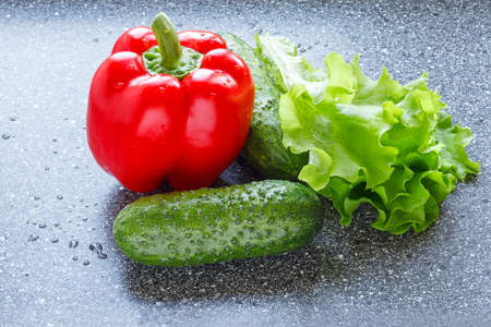 Red bell pepper or sweet pepper, little cucumbers and lettuce leaves on dark background, washed, with water drops, appetizing, closeup