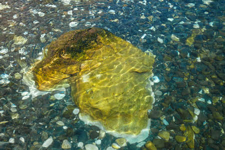 Big yellow stone and colorful pebbles under clear teal water, background or texture Banco de Imagens