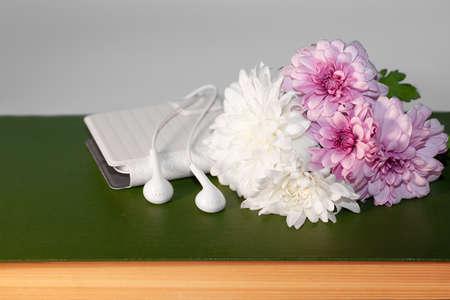 Fleurs blanches et roses de chrysanthème, téléphone, écouteurs et vieux livre sur fond clair, concept d'ambiance romantique, concept de moderne et vintage, ambiance printanière, détente et harmonie