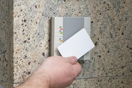 abrir puerta: el hombre pone la tarjeta en el lector de acceso