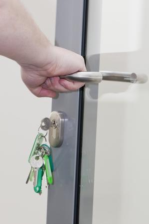 human hand on the door handle, keys in the lock doors