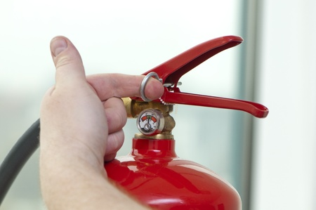 white hand pulls the pin from the extinguisher