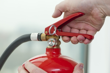 fire safety: white hand presses the trigger fire extinguisher