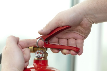 white hand presses the trigger fire extinguisher photo