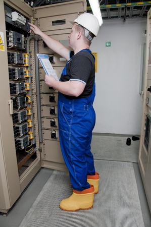protective clothing: electrician in the distribution of electricity in protective clothing Stock Photo