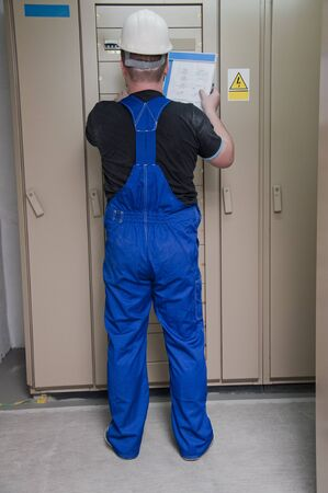 electrician in the distribution of electricity in protective clothing photo