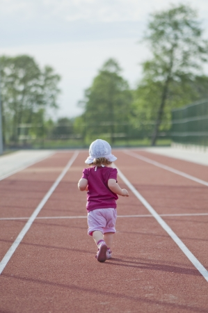 little girl runs across the track