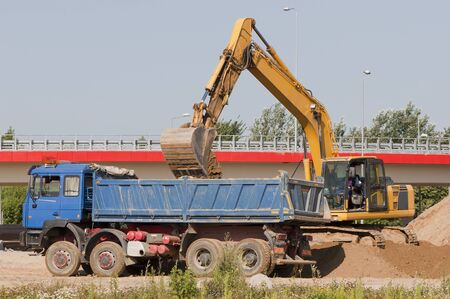 Excavator loading a truck on a construction site  photo