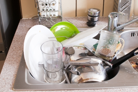 messy kitchen: dishes in the sink - mess in the kitchen Stock Photo