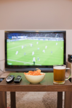 beer, chips and remote controls on the table  in the background TV - football game