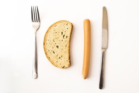 sausage, bread and cutlery on white background photo