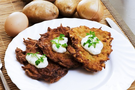 potato pancake with sour cream and parsley photo