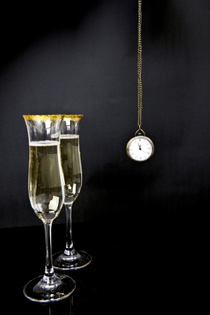 Two glasses of champagne and watch on a black background photo