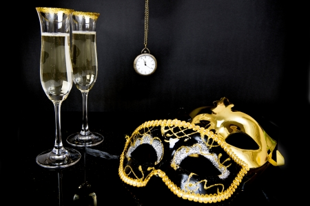 two glasses of champagne, two Venetian masks and watch on a black background photo
