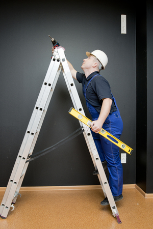 man climbing: worker with tools, stands on a ladder