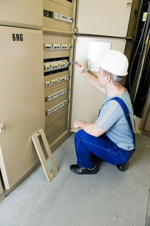 switchboard: electrician repairing something in the electrical switchboard Stock Photo
