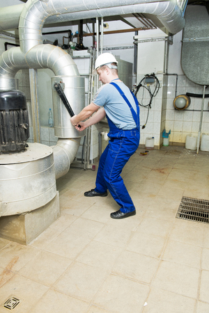 turns: worker in protective helmet turns valve Stock Photo