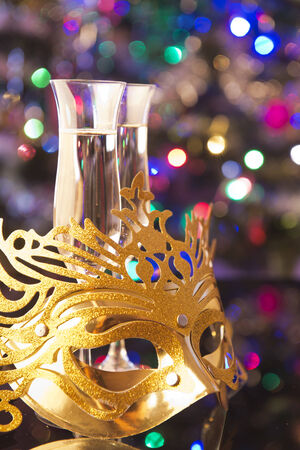 Two glasses of champagne and venetian mask on shiny  photo
