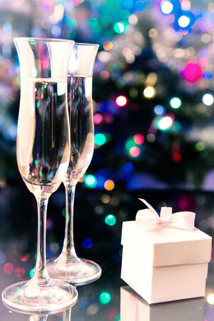 two glasses of champagne nad gift on shiny background