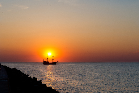 sunset - sailing ship silhouette on the sunset background photo