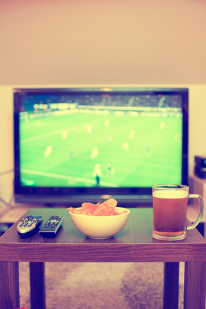 beer, chips and remote controls on the table (in the background TV - football game) photo