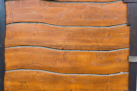 positioned: wooden background, horizontally positioned boards and rope