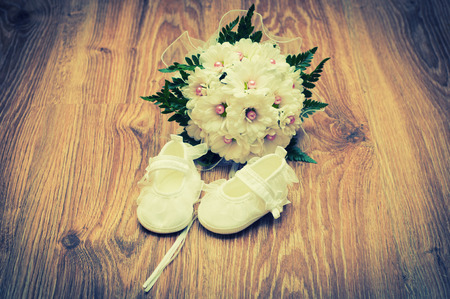 White shoes and white bouquet on a wooden floor photo