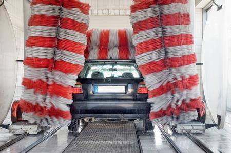 black car at the car wash - a huge brush