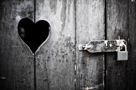 prisoner of love: Old door with a heart padlocked