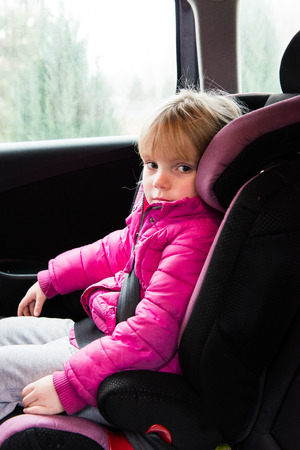buckled: little girl in a pink jacket sitting in a car seat