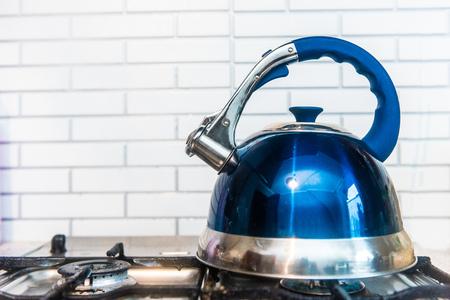 gas cooker: blue teapot stands on a gas cooker