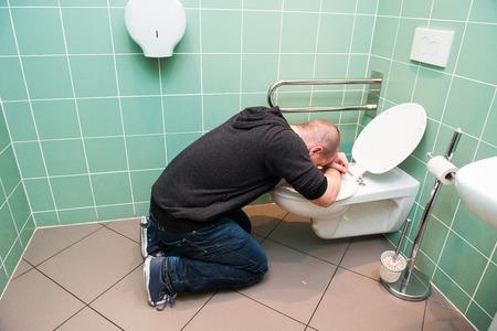 man kneeling: Man kneeling and vomiting in the toilet