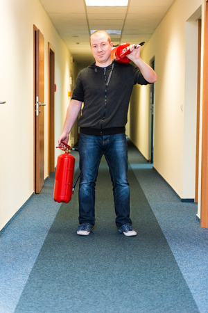 fire extinguishers: white man holding two fire extinguishers