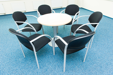 roundtable: table and six chairs on the blue carpet