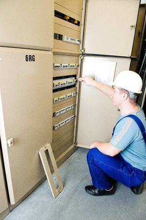tightened: electrician tightened something in the electrical switchboard