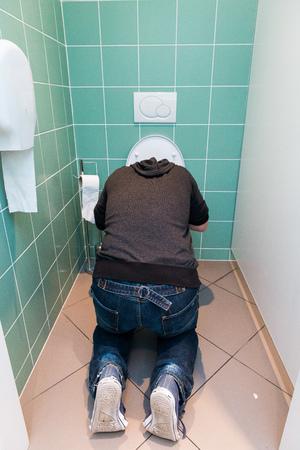 vomito: El hombre de rodillas y v�mitos en el inodoro Foto de archivo