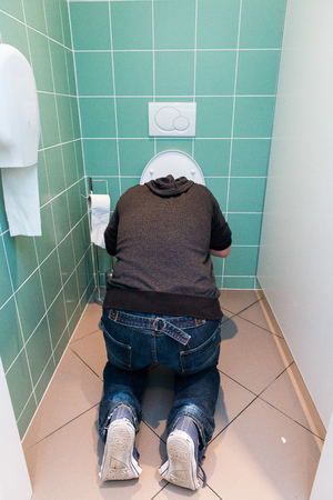 infirm: Man kneeling and vomiting in the toilet