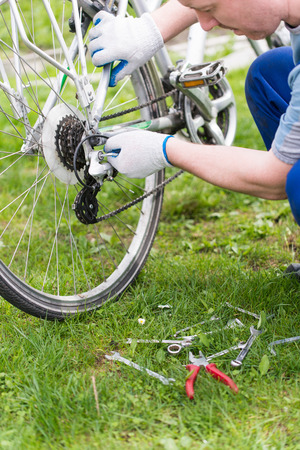 specialized job: man is fixing the bike. Adjust gears Stock Photo