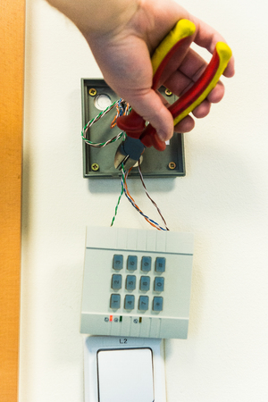 disarm: man crosses the wires in the numeric panel. closeup to device
