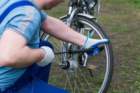 air bladder: Man pumping wheel bike. preparation for the bike season Stock Photo