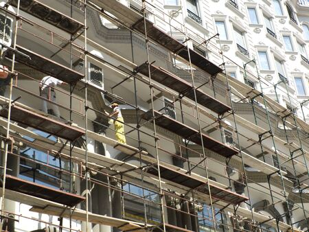 manual job: Workers on scaffold working on the facade of a new building -architecture  Editorial