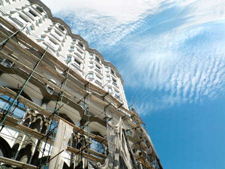 scaffold: Building under construction with mounted scaffold and  sky with cirrus clouds in the background