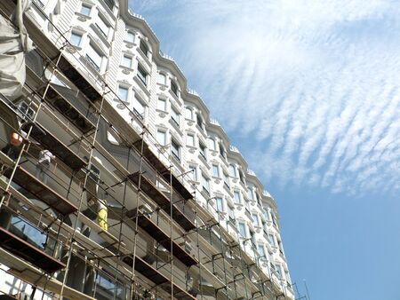 manual job: Workers on scaffold working on the facade of the new building and  sky with cirrus clouds Editorial