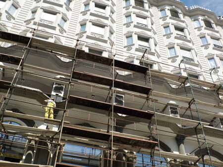 manual job: Worker on scaffold working on the facade of the new building-architecture  Editorial