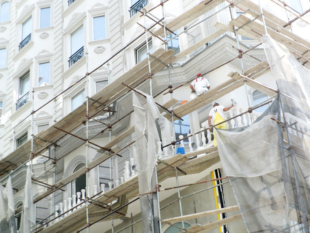 manual job: Worker on scaffold working on the facade of a new building-architecture