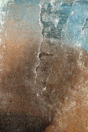gravelly: Small part of plastered hoarse,scratched and peeled surface area with blue and brown paint -Abstract background-Close up